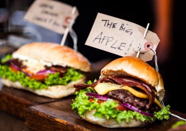 Close up colour image of two freshly flame grilled burgers next to each other on a market stall at Borough Market, a famous food market in London, UK. The burgers are stuffed with bacon, melted cheese, fresh lettuce and red onion. The burger in the foreground has a label attached to it that says 'The Big Apple'. Horizontal image with copy space.